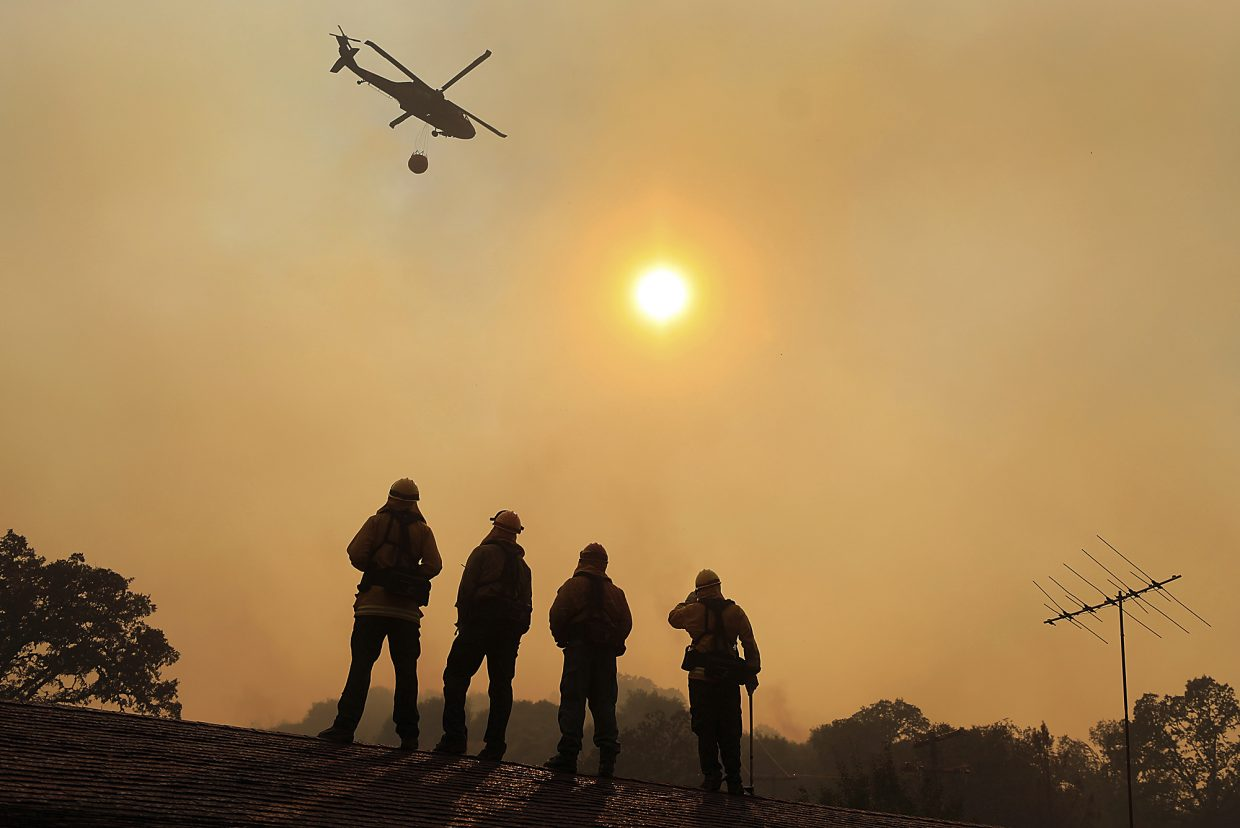 Firefighters stand watch on a roof as a wildfire sweeps through the area near Lakeport, Calif., Thursday, August 2, 2018.