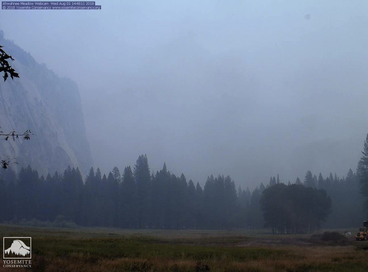 In this Wednesday, Aug. 1, 2018 image from a Yosemite Conservancy webcam, smoke from wildfires obscures the Ahwahnee Meadow at Yosemite National Park, Calif. Yosemite National Park could reopen its scenic valley and other areas Monday, Aug. 6, 2018, if conditions improve after a 12-day closure due to nearby wildfires. The park's iconic cliffs have been shrouded in so much smoke that the air quality in Yosemite is currently worse than Beijing.