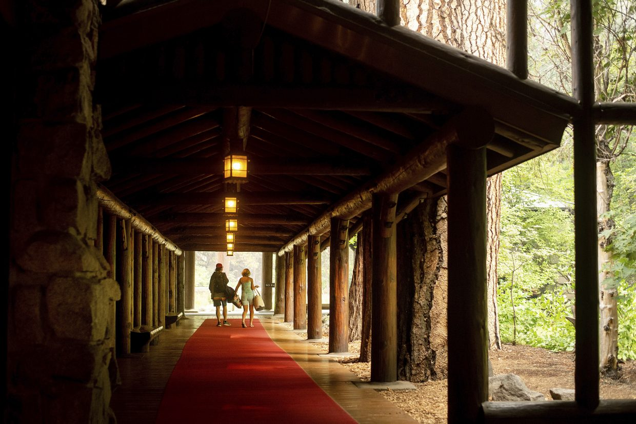 FILE - In this July 25, 2018 file photo, guests leave the The Majestic Yosemite Hotel, formerly The Ahwahnee Hotel, shortly after it closed in Yosemite National Park, Calif. Yosemite National Park could reopen its scenic valley and other areas Monday, Aug. 6, 2018, if conditions improve after a 12-day closure due to nearby wildfires. The park's iconic cliffs have been shrouded in so much smoke that the air quality in Yosemite is currently worse than Beijing.