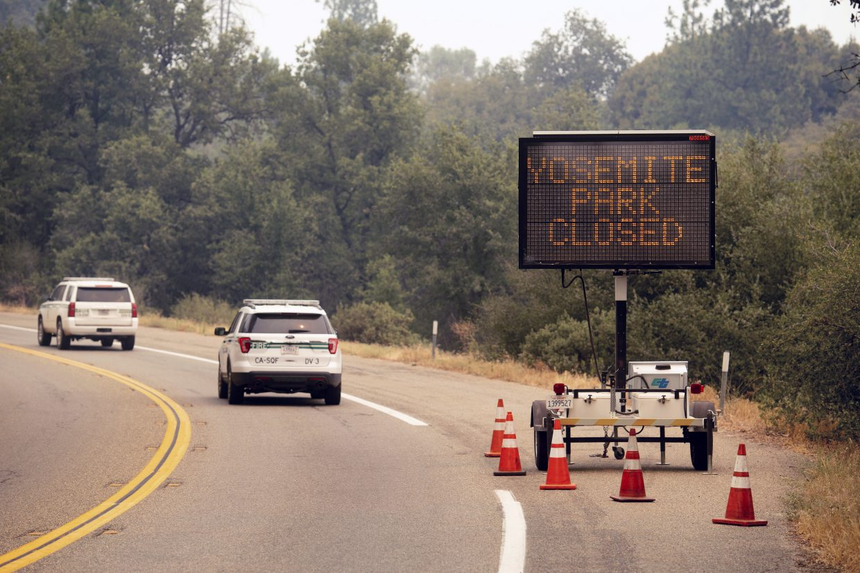 FILE - In this July 25, 2018 file photo, a sign on Highway 41 announces the closure of Yosemite National Park near Oakhurst, Calif. Yosemite National Park could reopen its scenic valley and other areas Monday, Aug. 6, 2018, if conditions improve after a 12-day closure due to nearby wildfires. The park's iconic cliffs have been shrouded in so much smoke that the air quality in Yosemite is currently worse than Beijing.
