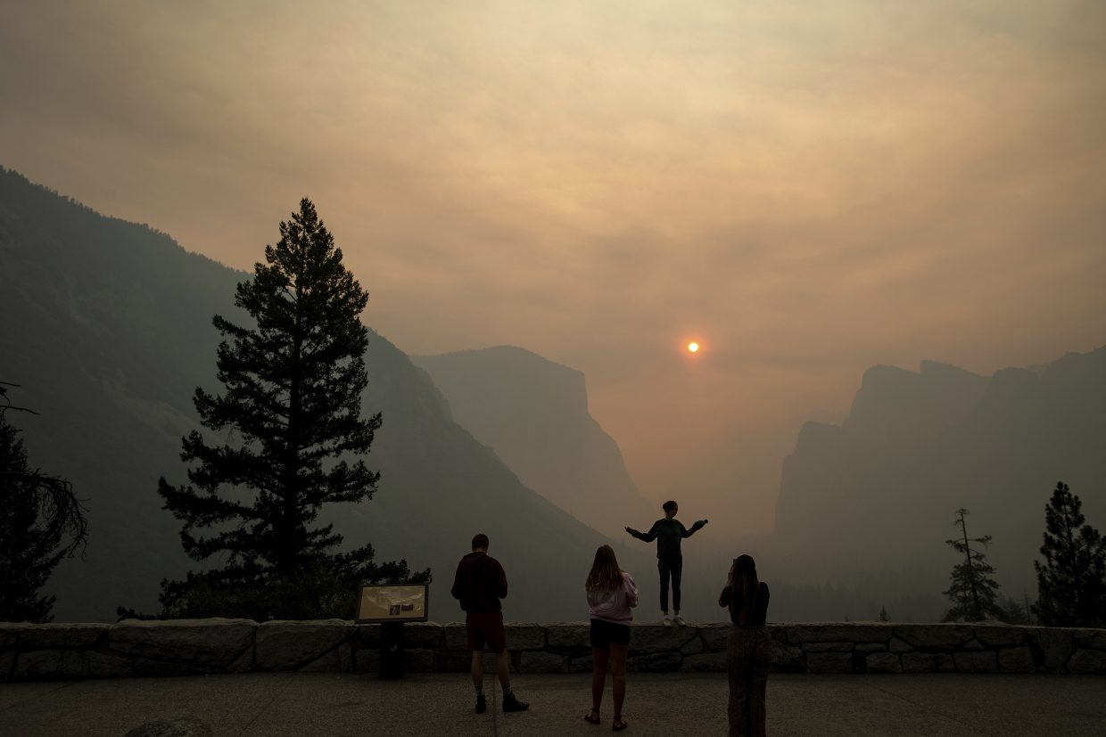 FILE - In this July 25, 2018 file photo, Hannah Whyatt poses for a friend's photo as smoke from the Ferguson fire fills Yosemite Valley in Yosemite National Park, Calif. Yosemite National Park could reopen its scenic valley and other areas Monday, Aug. 6, 2018, if conditions improve after a 12-day closure due to nearby wildfires. The park's iconic cliffs have been shrouded in so much smoke that the air quality in Yosemite is currently worse than Beijing.