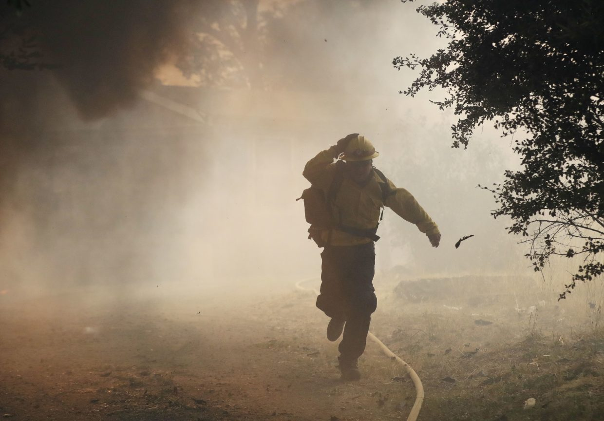 In this Monday, July 30, 2018, file photo, a firefighter runs from a burning structure, in Finley, Calif. Authorities say a rapidly expanding Northern California wildfire burning over an area the size of Los Angeles has become the state's largest blaze in recorded history. It's the second year in a row that California has recorded the state's largest wildfire.