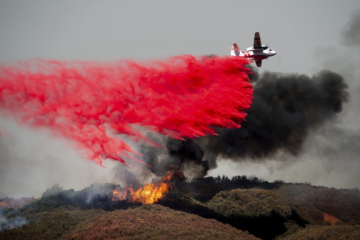 In this Monday, July 30, 2018, file photo, an air tanker drops retardant on a wildfire burning near Lakeport, Calif. Authorities say a rapidly expanding Northern California wildfire burning over an area the size of Los Angeles has become the state's largest blaze in recorded history. It's the second year in a row that California has recorded the state's largest wildfire.