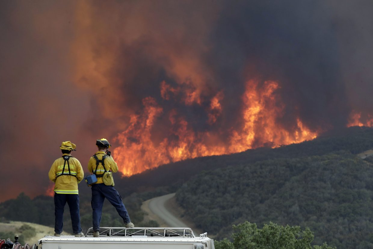 In this Tuesday, July 31, 2018, file photo, a fire crew from San Luis Obispo County keeps an eye on an advancing wildfire from the perimeter of a residence in Lakeport, Calif. Authorities say a rapidly expanding Northern California wildfire burning over an area the size of Los Angeles has become the state's largest blaze in recorded history. It's the second year in a row that California has recorded the state's largest wildfire.