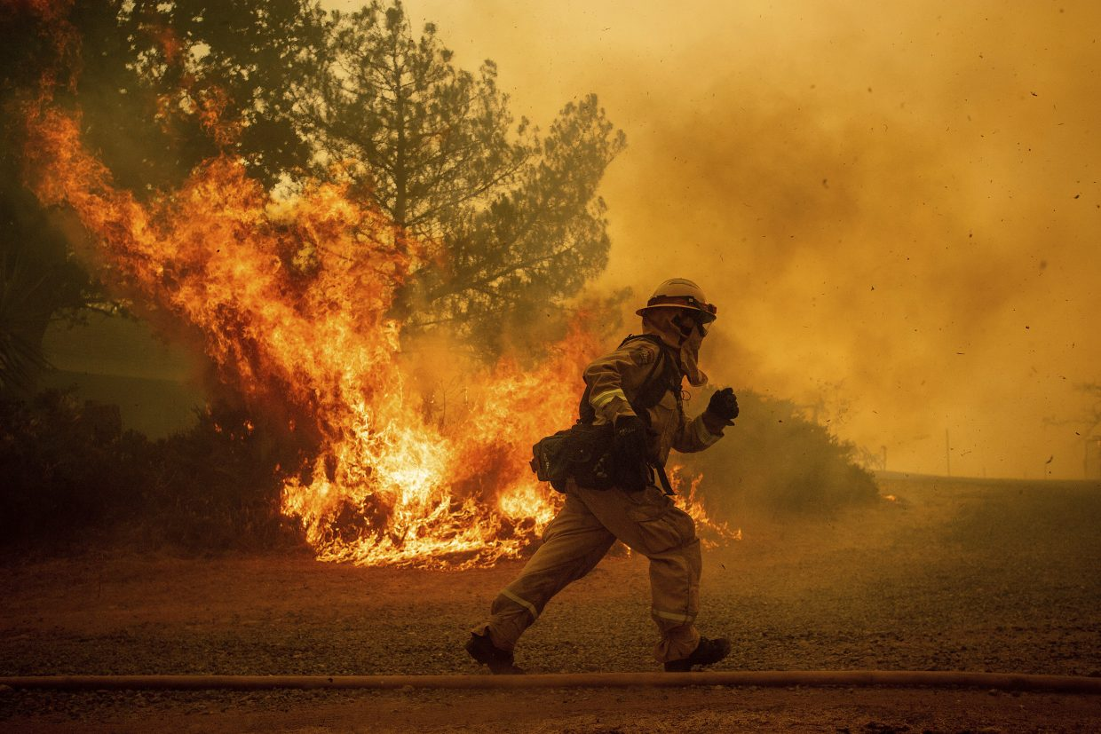 In this Tuesday, July 31, 2018, file photo, a firefighter runs while trying to save a home as a wildfire tears through Lakeport, Calif. The residence eventually burned. Authorities say a rapidly expanding Northern California wildfire burning over an area the size of Los Angeles has become the state's largest blaze in recorded history. It's the second year in a row that California has recorded the state's largest wildfire.
