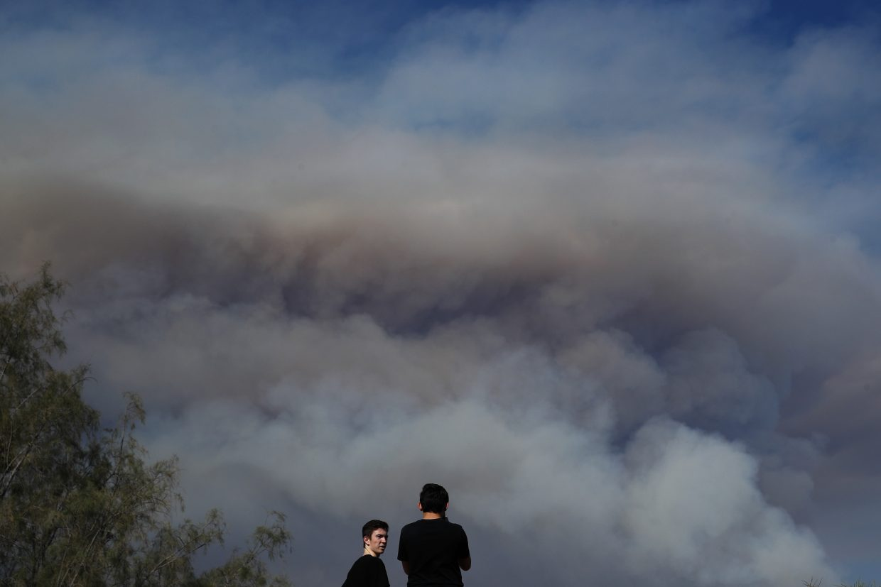 Two spectators watch as smoke from a wildfire burning near the Holy Jim area rises in the distance, Monday, Aug. 6, 2018, in Lake Forest, Calif. Authorities have evacuated cabins in two communities in the Santa Ana Mountains in Orange County because of a fast-moving wildfire.