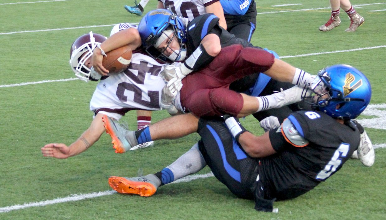 South Tahoe's James Knudsen (1) and Gio Medina Morales (6) team up to tackle an Elko running back.