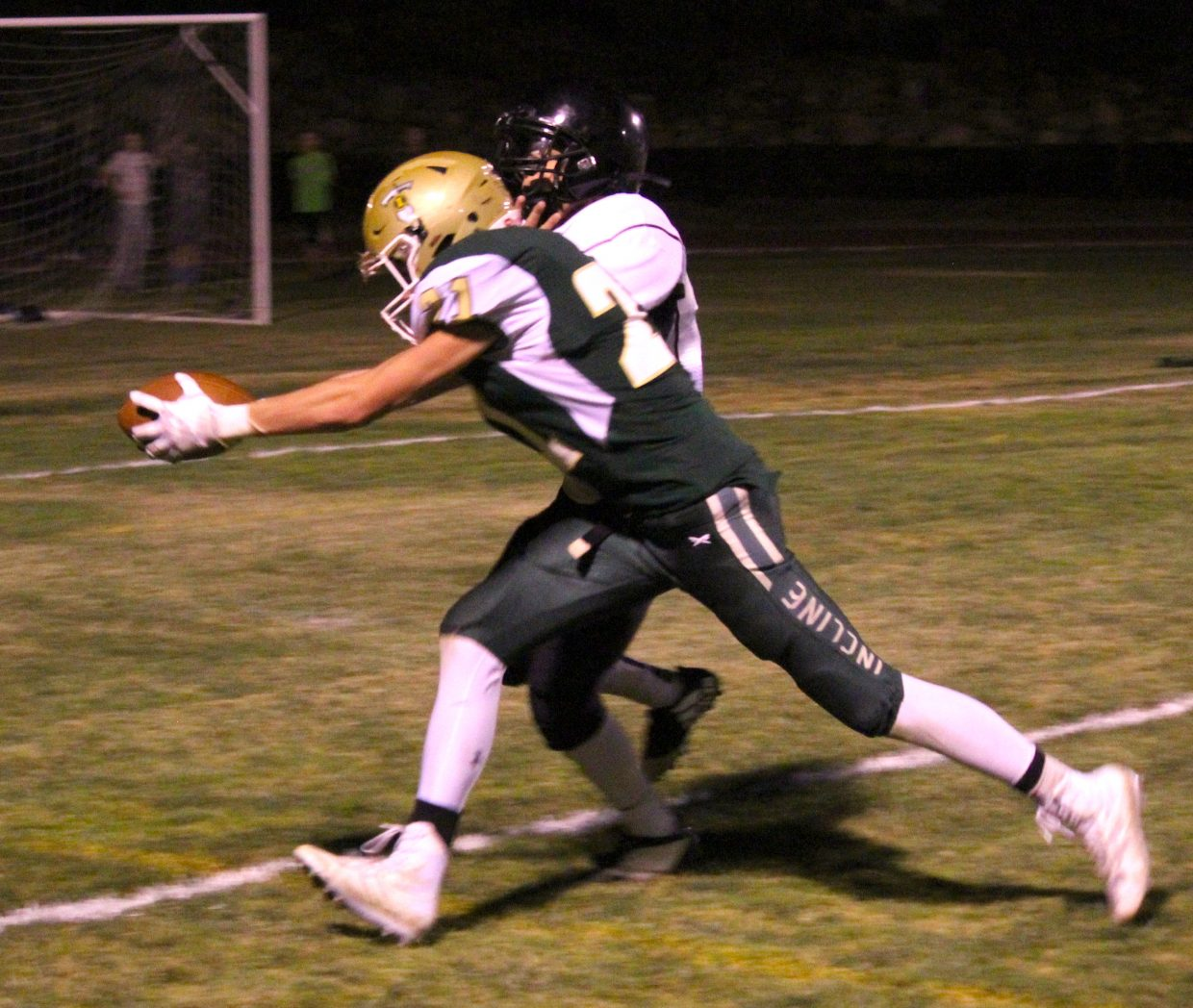 Incline's Gage Pierce reaches the ball across the goal line for a 12-yard touchdown run.