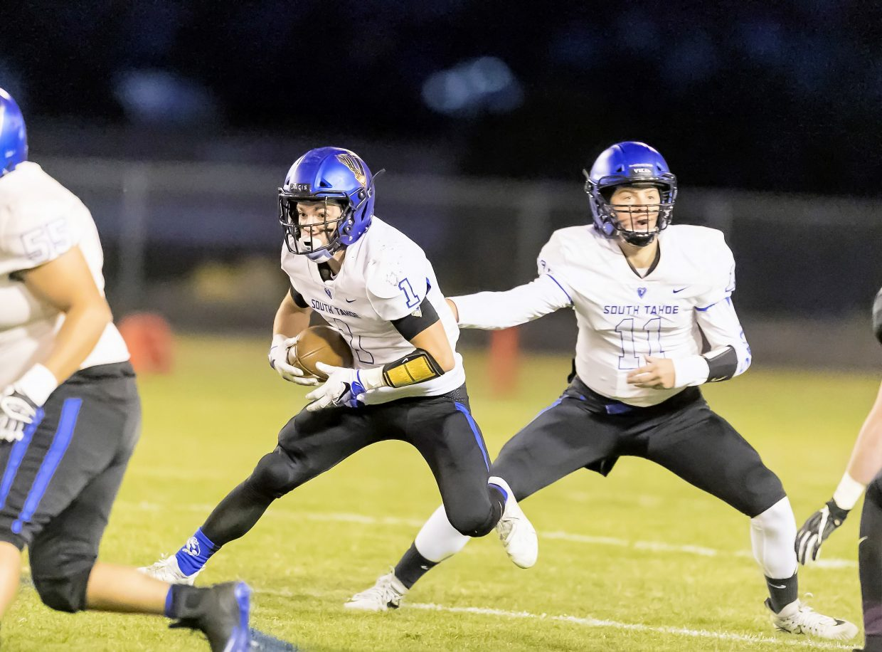 South Tahoe quarterback Jake Tarwater hands off to running back James Knudsen Friday at North Valleys.