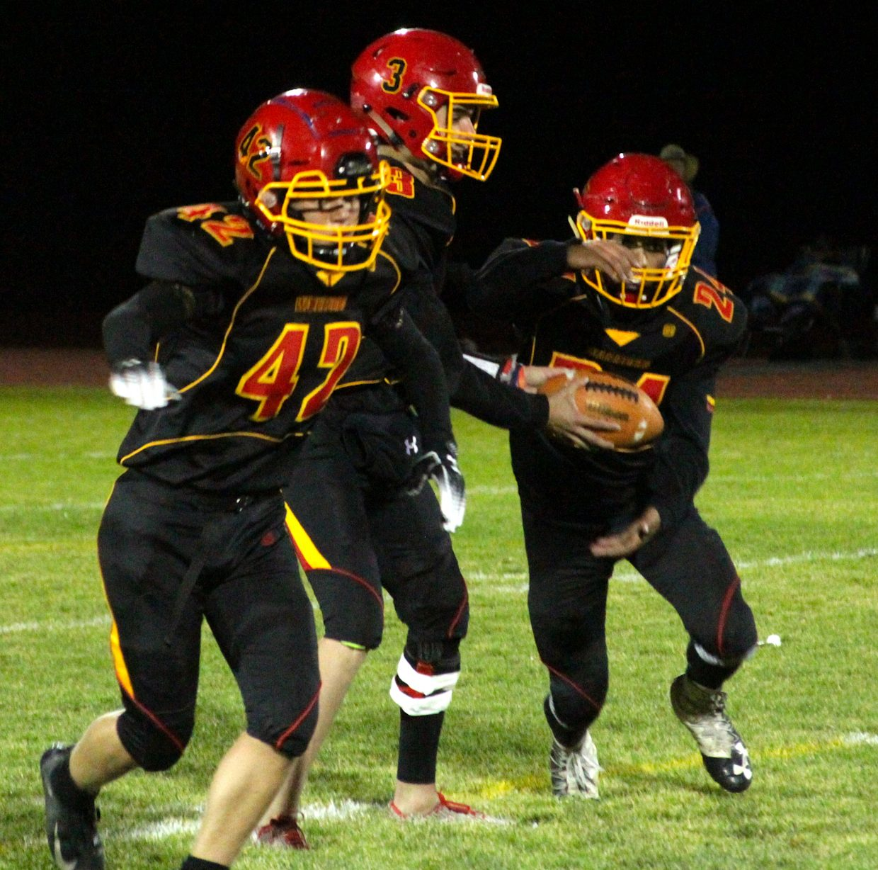Whittell quarterback Trent Dingman hands off to Isaiah Womack as Jack White (42) prepares to lead block.