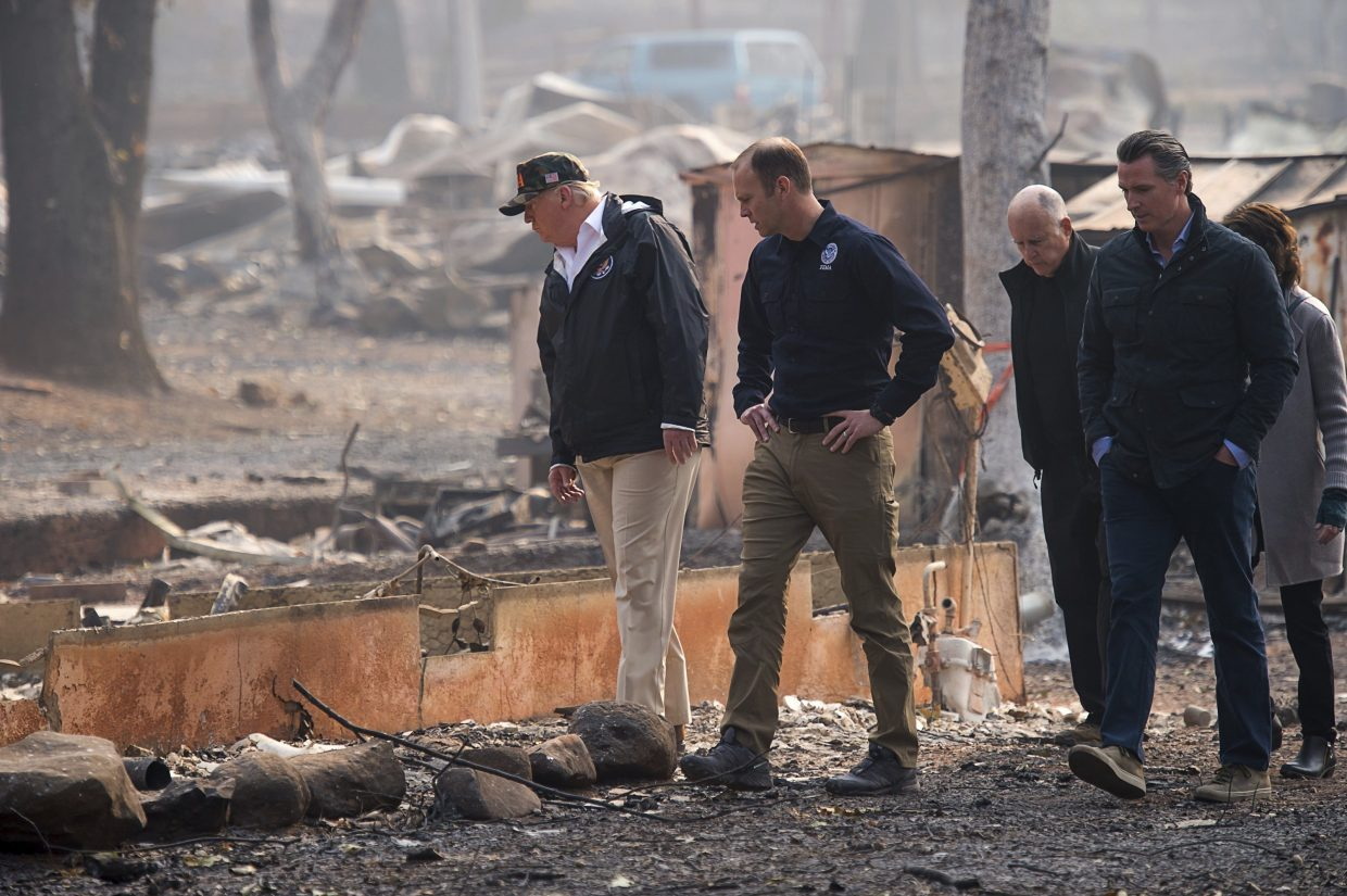 President Donald Trump, from left, FEMA Administrator Brock Long, California Gov. Jerry Brown, Gov.-elect Gavin Newsom and Paradise Mayor Jody Jones tour the Skyway Villa Mobile Home and RV Park during Trump's visit of the Camp Fire in Paradise, Calif., Saturday, Nov. 17, 2018. Trump went to Northern California on Saturday to survey the devastation from the nation's deadliest wildfire in a century.