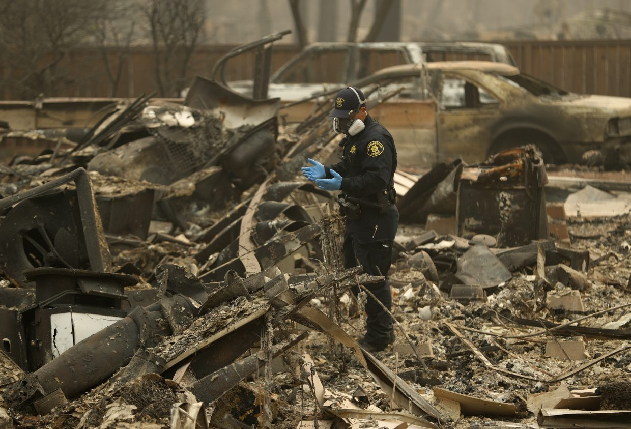 FILE - In this Thursday, Nov. 15, 2018 file photo, a Sheriff's deputy looks for human remains at a home burned in the Camp fire in Magalia, Calif. Searchers are in a race against time with long-awaited rains expected in the Northern California fire zone where dozens of bodies have been recovered so far. While the rain is good for tamping down the still-burning fire, it will turn the fire zone into a muddy mess and make it more difficult for crews to search.