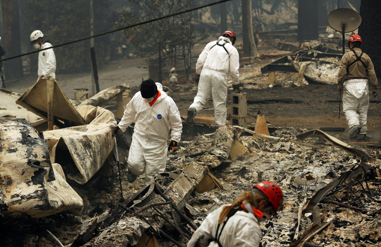 FILE - In this Tuesday, Nov. 13, 2018 file photo, search and rescue workers search for human remains at a trailer park burned out from the Camp fire in Paradise, Calif. Searchers are in a race against time with long-awaited rains expected in the Northern California fire zone where dozens of bodies have been recovered so far. While the rain is good for tamping down the still-burning fire, it will turn the fire zone into a muddy mess and make it more difficult for crews to search.