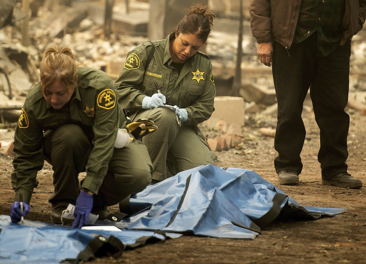FILE - In this Wednesday, Nov. 14, 2018, file photo, Sheriff's deputies recover the bodies of multiple Camp fire victims at the Holly Hills Mobile Estates residence in Paradise, Calif. Searchers are in a race against time with long-awaited rains expected in the Northern California fire zone where dozens of bodies have been recovered so far. While the rain is good for tamping down the still-burning fire, it will turn the fire zone into a muddy mess and make it more difficult for crews to search.