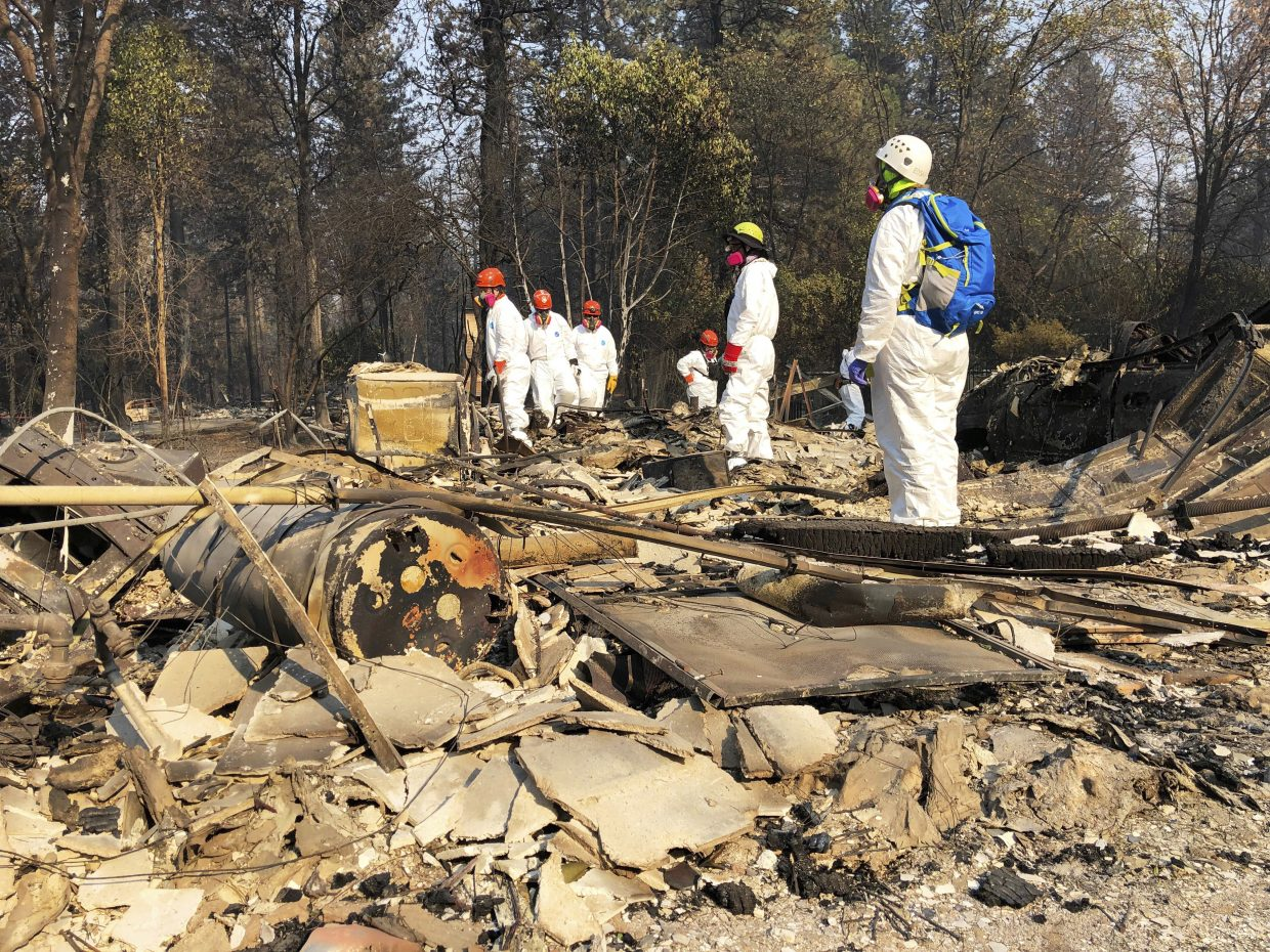 Volunteer members of an El Dorado County search and rescue team search the ruins of a home, looking for human remains, in Paradise, Calif., Sunday, Nov. 18, 2018, following a Northern California wildfire.