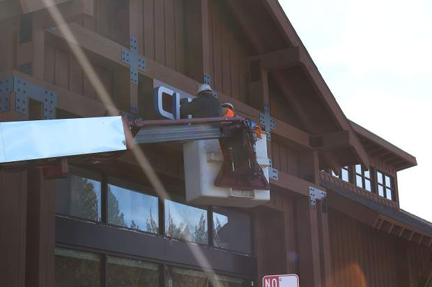 Construction workers install a Chase Bank sign on the front of a building that will be a future bank branch.