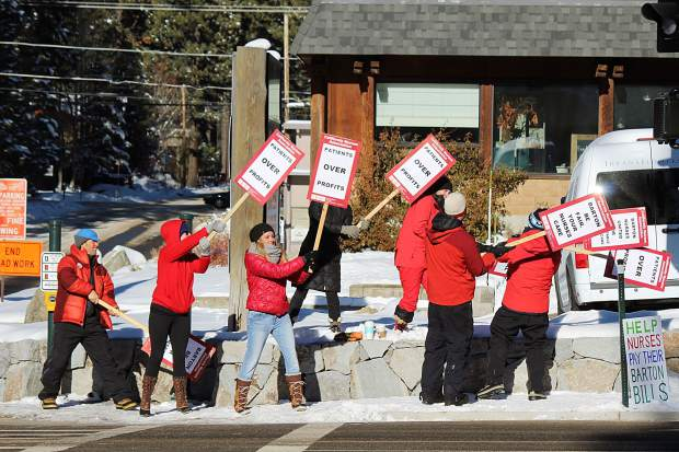 Demonstrators wave signs on the westbound side of Lake Tahoe Boulevard Monday morning.