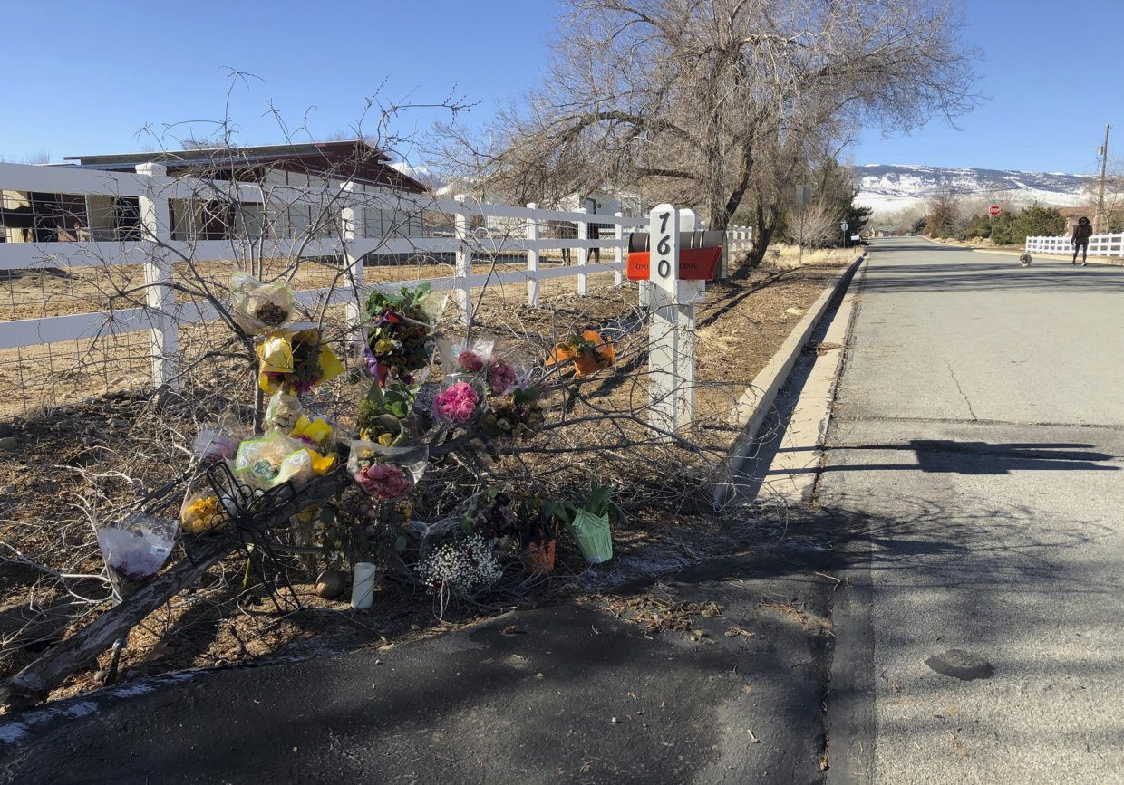 A makeshift memorial of several dozen bouquets and a candle are shown Thursday, Jan. 24, 2019, outside the south Reno, Nev., home of Gerald David, 81, and his 80-year-old wife, Sharon, whose bodies were found inside on Jan. 16. Authorities have arrested a man on suspicion of being in the U.S. illegally in the deaths of the Davids and two other people over the past two weeks. (AP Photo/Michelle L. Price)