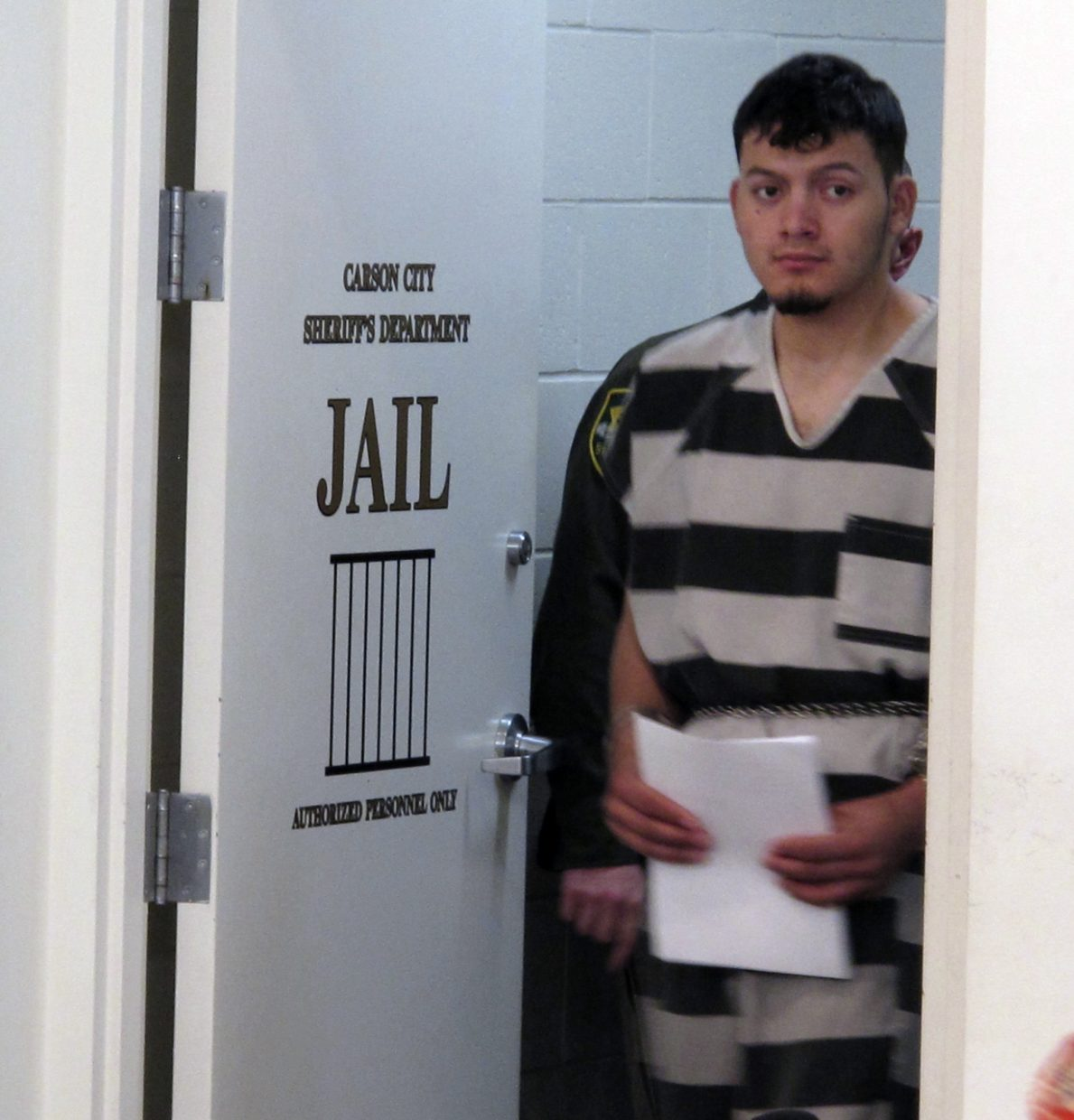 Wilber Ernesto Martinez-Guzman, 19, of El Salvador, is escorted into the courtroom for his initial appearance in Carson City Justice Court, Thursday, Jan. 24, 2019, in Carson City, Nev. Martinez-Guzman was arraigned on 36 felonies including two dozen weapon charges. He's a suspect in a series of four homicides earlier this month in Reno and south of Carson City in rural Gardnerville. Prosecutors say additional charges are pending.