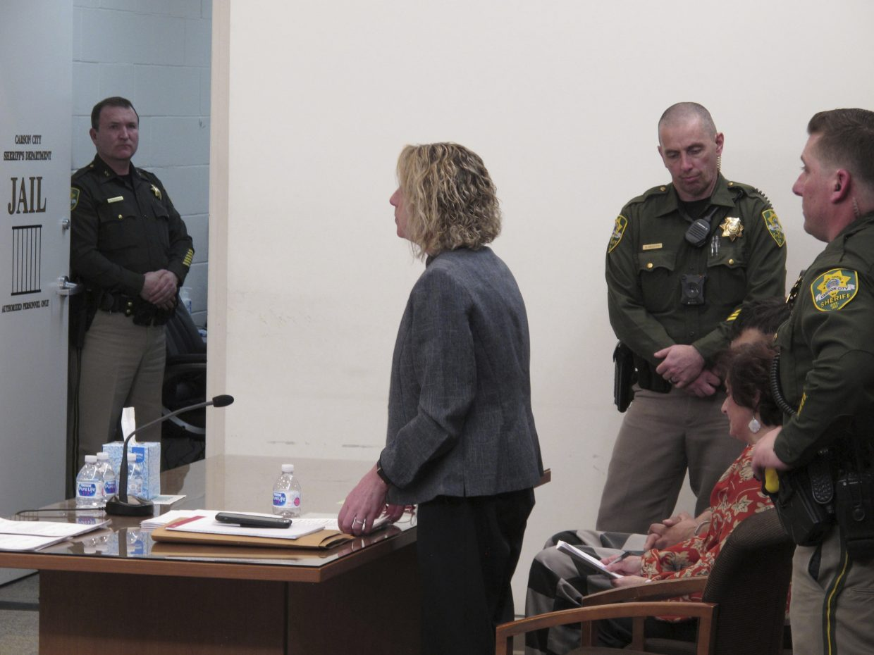 Nevada state public defender Karin Kreizenbeck speaks during the arraignment for Wilber Ernesto Martinez-Guzman, seated, 19, of El Salvador, in Carson City Justice Court on Thursday, Jan. 24, 2019, in Carson City, Nev. An interpreter and Martinez-Guzman in striped jail clothes are seated behind her between two Carson City sheriff's deputies. Martinez-Guzman is a suspect in four fatal shootings in Nevada and was accused in court Thursday of being in the U.S. illegally and selling jewelry stolen from some of the dead.