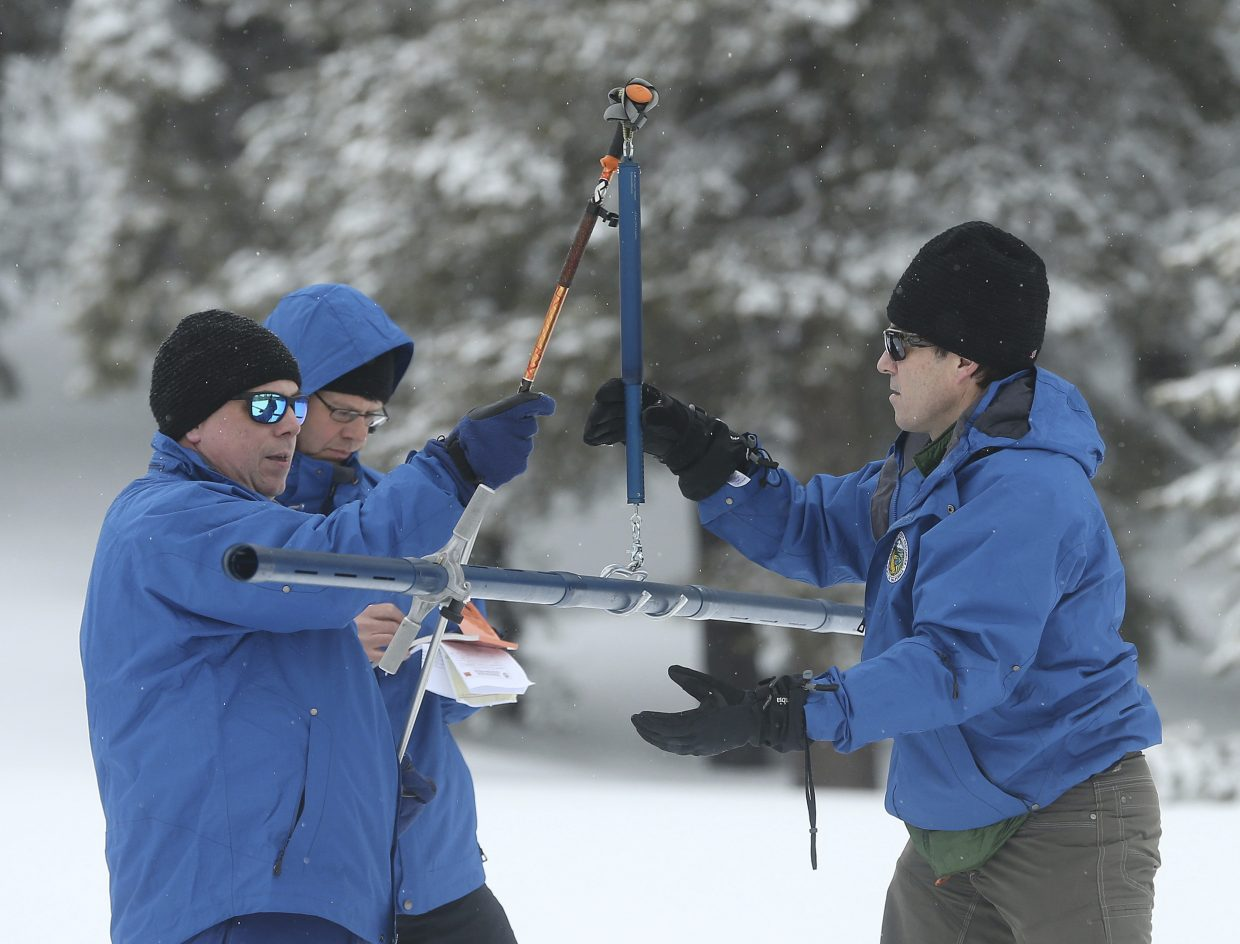 John King, right, of the Department of Water Resources, places the snowpack survey tube on a scale held by DWR climatologist Michael Anderson left, during the third manual snow survey of the season at the Phillips Station near Echo Summit, Calif., Thursday, Feb. 28, 2019. The survey found the snowpack at 113 inches deep with a snow water equivalent of 43.5 inches at this location at this time of year.