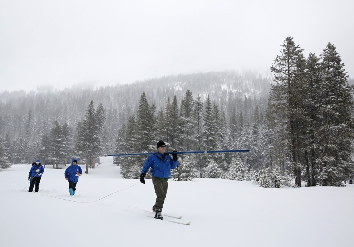 John King, right, of the Department of Water Resources, carries the snowpack measuring tube as he crosses a meadow while conducting the third manual snow survey of the season at the Phillips Station near Echo Summit, Calif., Thursday, Feb. 28, 2019. The survey found the snowpack at 113 inches deep with a snow water equivalent of 43.5 inches at this location at this time of year.