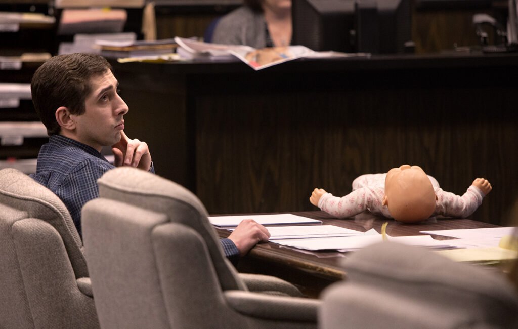 With a life-sized baby doll lying nearby, murder defendant Michael Swope listens Tuesday as his attorney tries to convince a jury that there is reason to doubt that his client killed a 6-week-old baby he had learned was another man's child.
