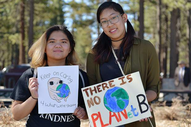 Darlene Padayhag, left, and Mariel Penollar show homemade climate signs before marching in the third annual Earth Day Climate March on April 27. Penollar is a local college student, studying ecology and convinced Padayhag to accompany her.
