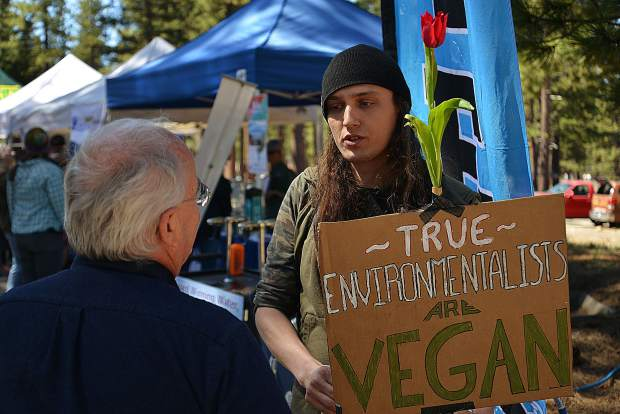 Aaron Skinner speaks with interested community members about the environmental benefits of veganism at Bijou Park's Earth Day celebration on April 27. Skinner cited increased carbon footprints and water consumption rates as just a few reasons to consider veganism.