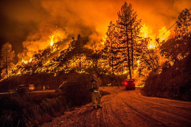 In this 2015 photo, fire crews run controlled burns at night to contain the Butte Fire near Arnold, Calif.