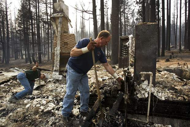 In this 2007 photo, men clear debris after the Angora Fire destroyed hundreds of Tahoe-area homes south of Kings Beach, Calif. Situated on the pristine north shore of Lake Tahoe, Kings Beach is one of the most heavily visited vacation spots in Northern California. That's a big part of the problem. Because so much of the population comes and goes, it becomes harder to get people to treat wildfire risk with the respect it deserves. (Paul Kitagaki Jr./The Sacramento Bee via AP)