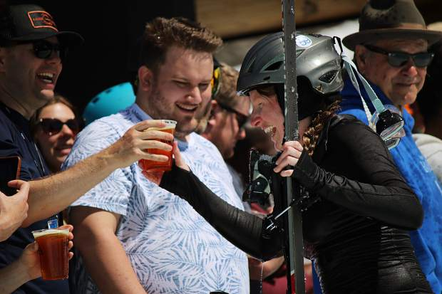 A competitor hands a beer back to spectator after having to jump back into the pond to retrieve a ski at Heavenly Mountain Resort's pond skim.