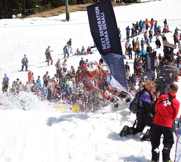 A snowboarder nearly takes out several photographers at the 2019 pond skim at Heavenly Mountain Resort.