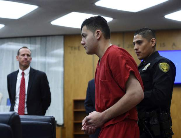 Washoe County District Attorney Christopher Hicks, left, looks on as Wilber Martinez-Guzman, from El Salvador, appears in Washoe District Court in Reno, Nev., on Monday, May 20, 2019. Martinez-Guzman faces murder, burglary and weapons charges in the deaths of four people in northern Nevada in January.