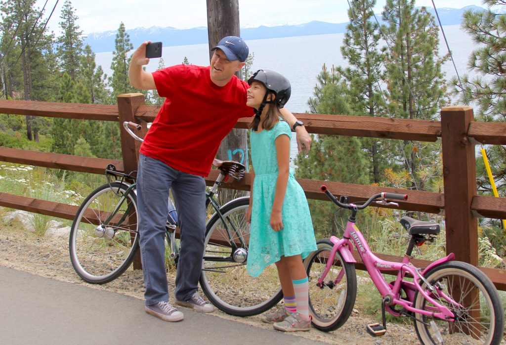 A father and daughter stop for a selfie with Lake Tahoe in the background.