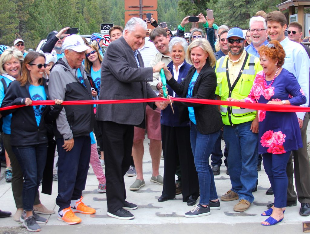Nevada Gov. Steve Sisolak helps cut the ribbon Friday to open the East Shore Trail at Lake Tahoe.
