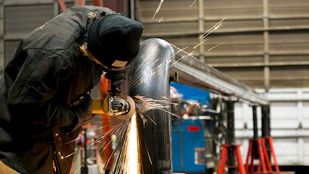 A Village Terrain Park Crew member welds a rail for Superpark 22.