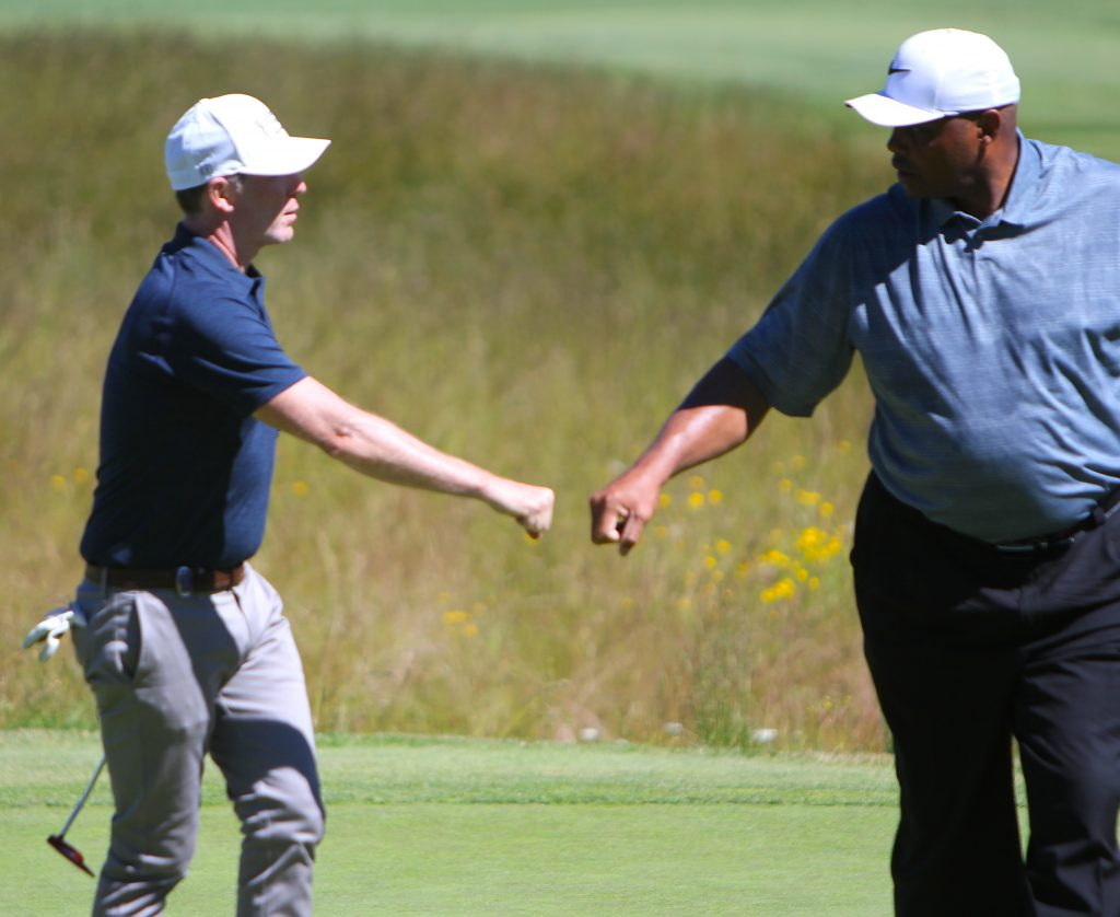 Bobby Flay receives a fist bump from Charles Barkley after knocking it stiff on No. 11 and converting a birdie.