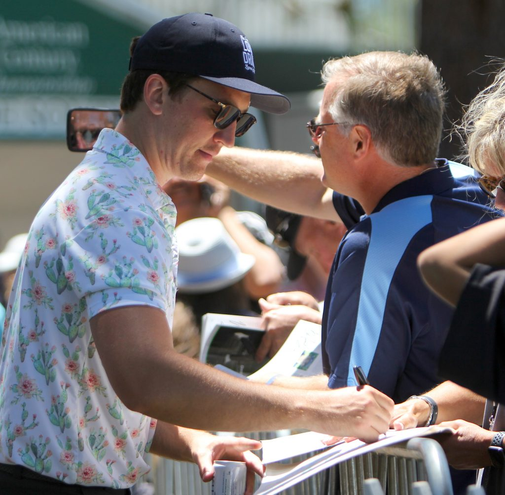 Miles Teller signs autographs after his second round.