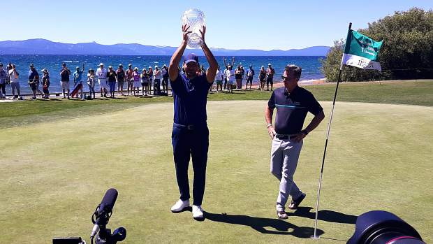 2019 champion Tony Romo raises the trophy for a second straight year.