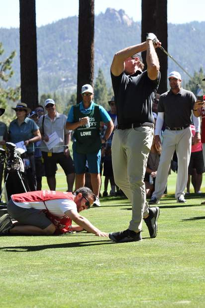 Jeremy Roenick hits a tee shot that was placed between a man's fingers Thursday.