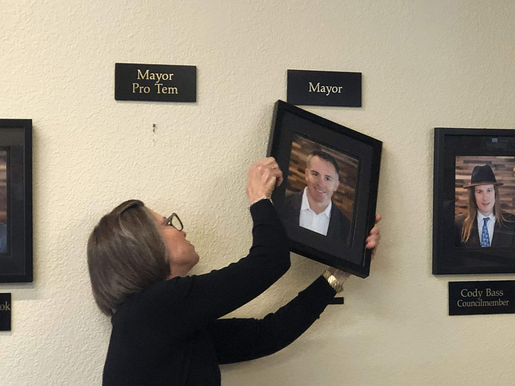 South Lake Tahoe City Clerk Sue Blankenship changes photos at City Hall.