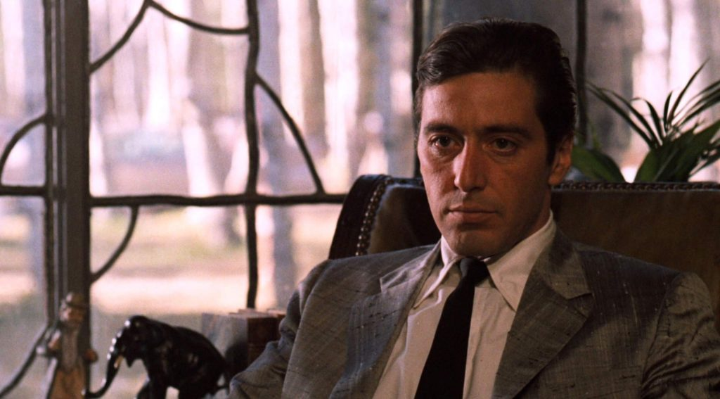 """Michael Corleone, played here by Al Pacino, sits at his desk as he tries to hatch business deals with corrupt politicians during a scene from """"The Godfather: Part II."""" Through the window, the viewer can see the distinctive forest of the Lake Tahoe Basin."""