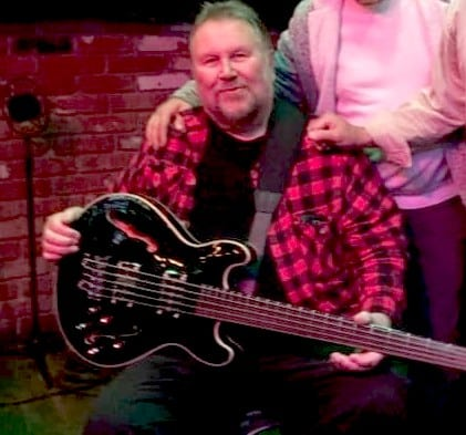 Local musician Charlie Schofield poses with his bass guitar.