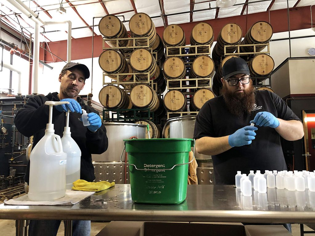 Andy Barr (left) and Jake Holshue fill bottles with hand sanitizer at Old Trestle Distillery's location.