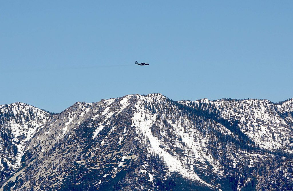 The lead C-130 airplane flies over Lake Tahoe's West Shore Tuesday.