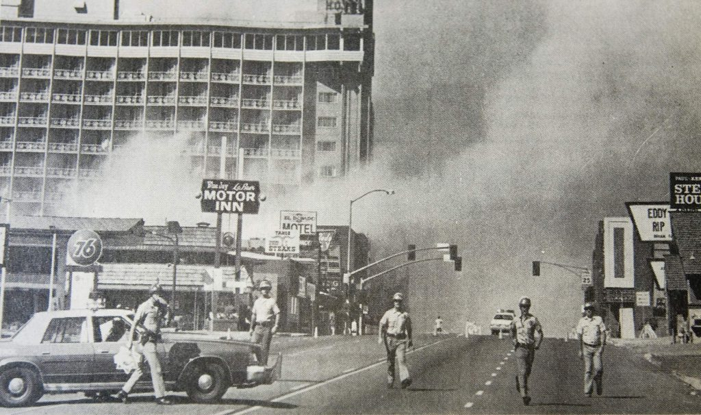 Lake Tahoe police and El Dorado County sheriff's deputies keep the crowd of onlookers off of Highway 50 after the detonation of the bomb at Harveys in August 1980.