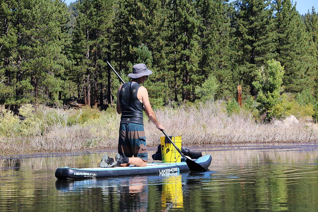Volunteer citizen scientists survey Spooner Lake from a paddle board.