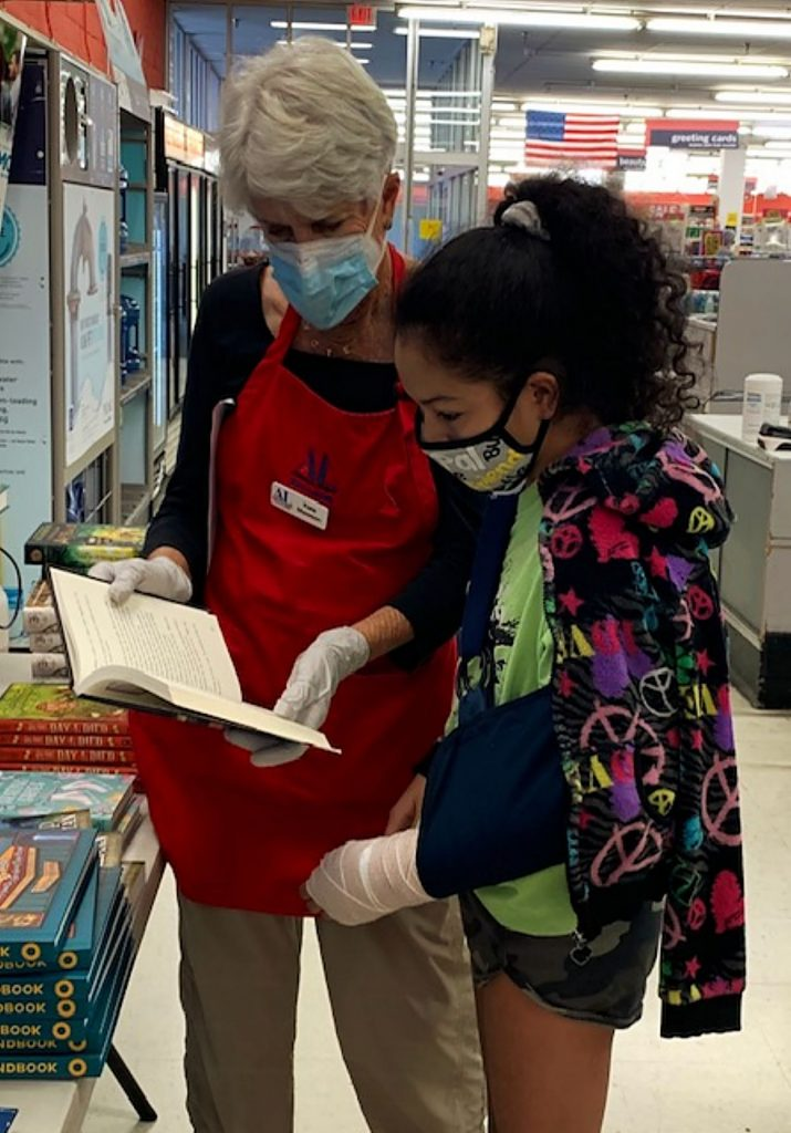 Assistance League volunteer Kate Mawson and a student receiving a new book.